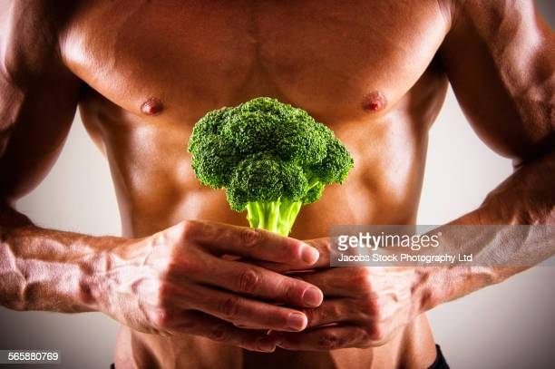 Muscular Caucasian athlete holding broccoli