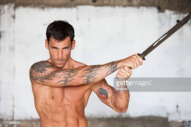 Muskuläre fighter mit tattoos und Schwert blade