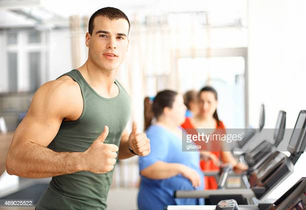 muscular guy exercising on treadmill. - sleeveless top stock pictures, royalty-free photos & images