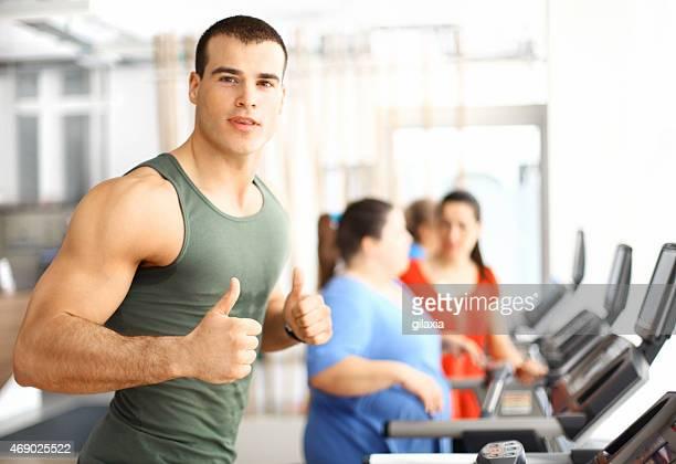 Muscular guy exercising on treadmill.