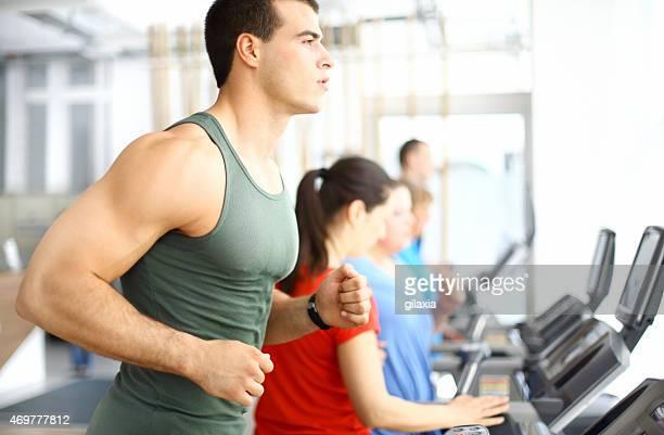 muscular guy ejercítes'en la máquina trotadora. - sin mangas fotografías e imágenes de stock