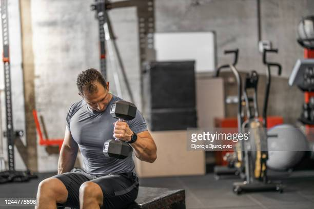 muscular guy in sportswear lifting dumbbell while sitting on bench at cross training gym. mature athlete using dumbbell during a workout. strong man under physical exertion pumping up bicep muscle with heavy weight. - mid adult stock pictures, royalty-free photos & images