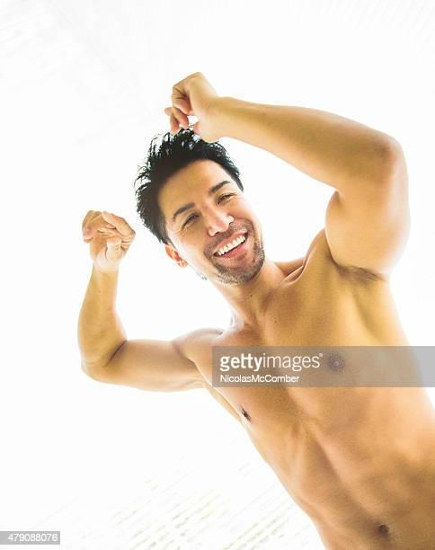 Muscular Japanese man dancing smiling fun back lit waist up