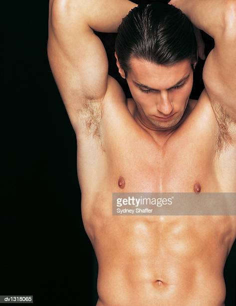 Muscular Male Nude With His Arms upstretched and Looking Down