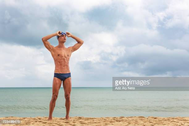 muscular male swimmer standing on beach putting on swimming goggles - zwembroek stockfoto's en -beelden