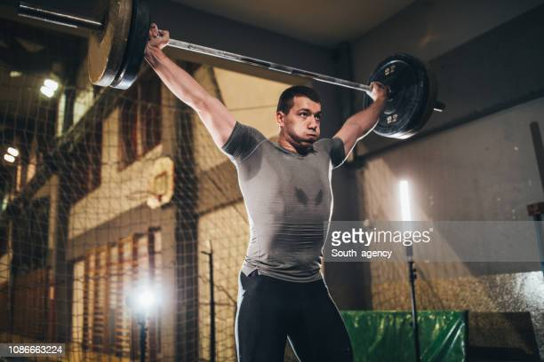 muscular man deadlifting barbell - snatch weightlifting stock photos and pictures
