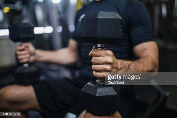 muscular man doing weighted exercises - human arm stock pictures, royalty-free photos & images