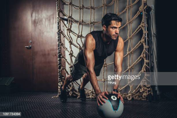 muscular man exercises plank pose on medicine ball - medicine ball stock pictures, royalty-free photos & images