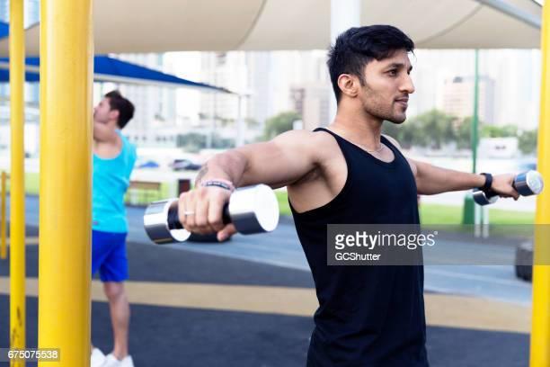 Hombre musculoso haciendo ejercicio en un gimnasio al aire libre cerca de Dubai Marina