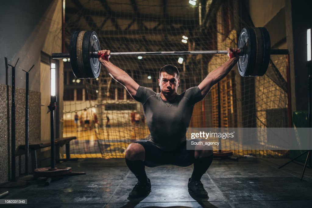 Muscular man exercising with barbell in gym : Stock Photo
