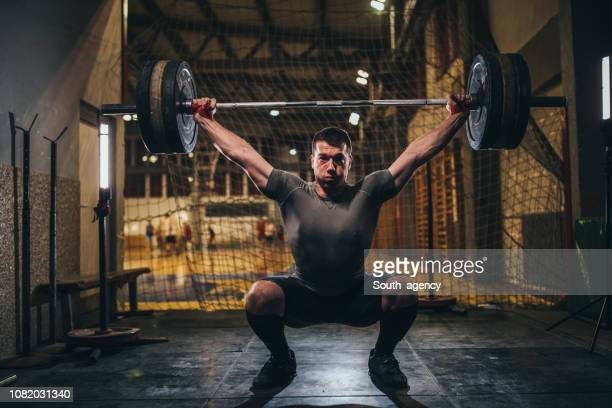 muscular man exercising with barbell in gym - snatch weightlifting stock photos and pictures
