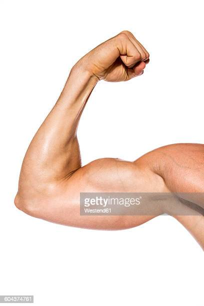 Muscular man flexing his biceps in front of white background, close-up