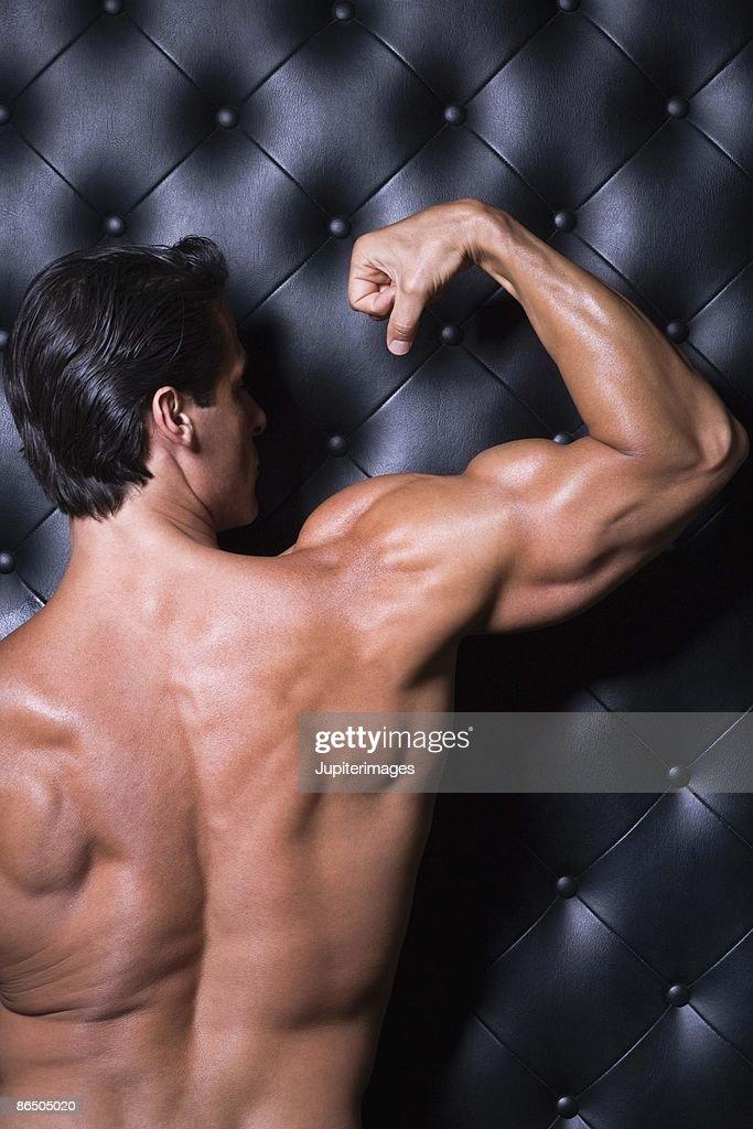 Muscular man flexing : Stock Photo