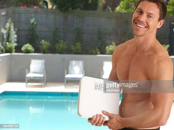 Muskuläre Mann hält Waage im Badezimmer