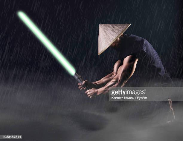 muscular man holding laser sword against black background - lightsaber stock pictures, royalty-free photos & images