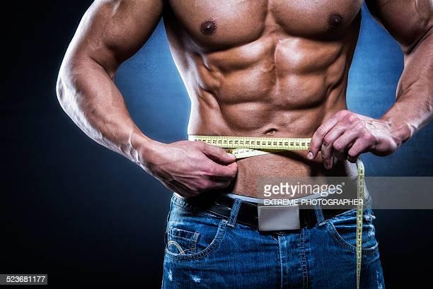 Muskuläre Mann hält Maßband
