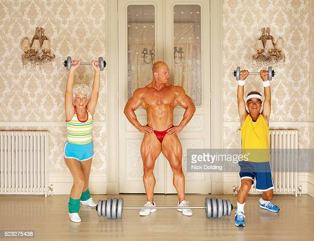 muscular man looking at two seniors weightlifting - bodybuilding stock-fotos und bilder