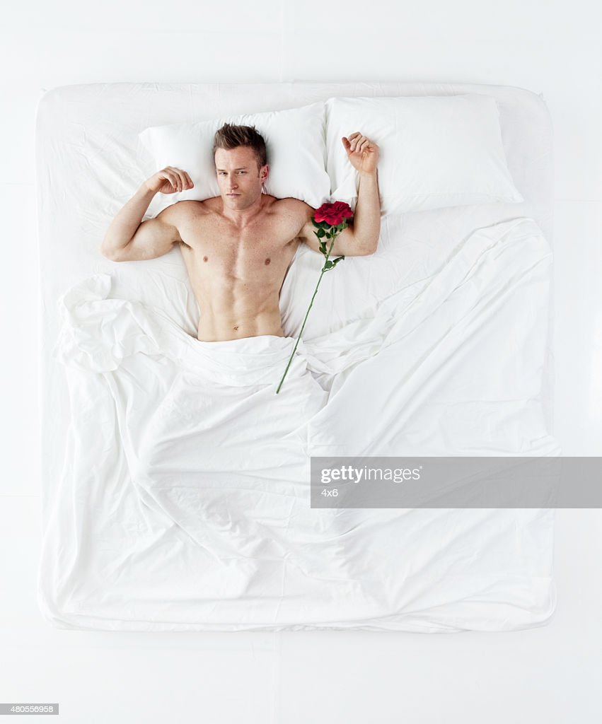 Muscular man lying on bed : Stock Photo