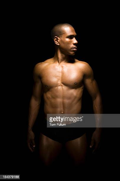 Muscular man posing against a black background