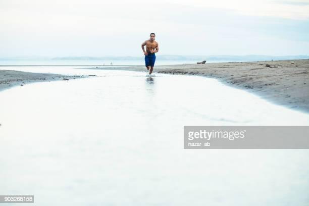 Muscular man running at beach.