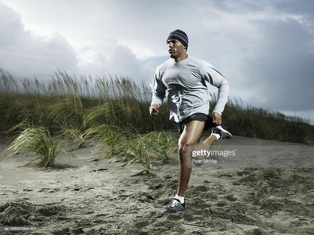 Muscular man running on beach : Stock Photo
