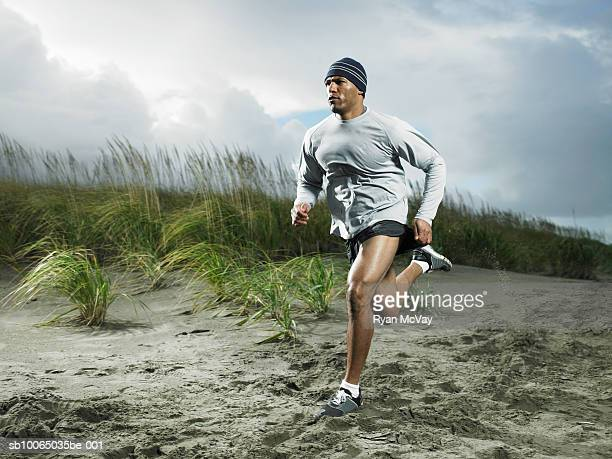 muscular man running on beach - black shorts stock pictures, royalty-free photos & images