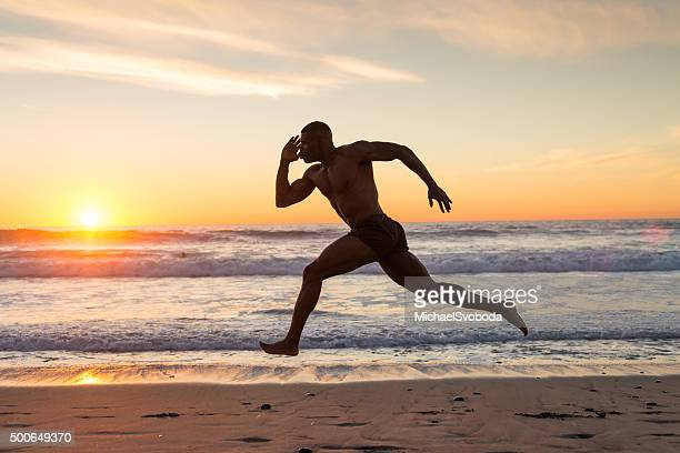 Muscular Man Running On The Beach At Sunset