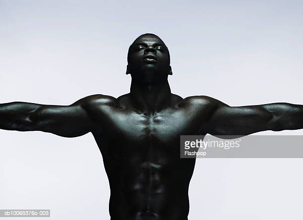 Muscular man standing with arms out, close-up