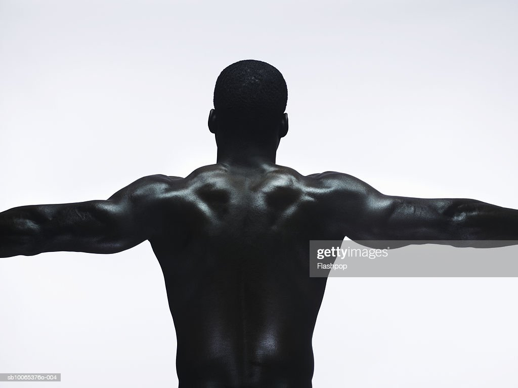 Muscular man standing with arms out, rear view, close-up : Foto stock