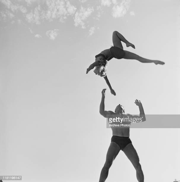 A muscular man throws a female acrobat into the air and prepares to catch her circa 1955