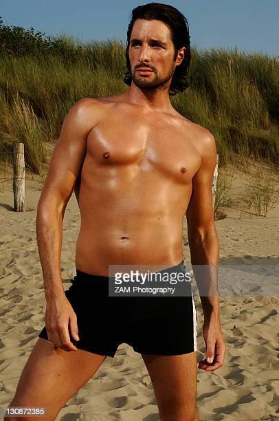 Muscular man wearing swimming trunks posing on beach