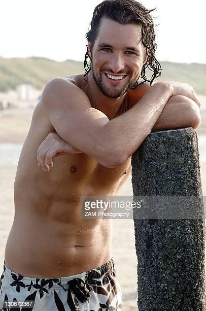 Muscular man wearing swimming trunks standing on a beach