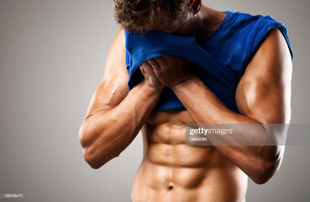 muscular man wiping of sweat with his t-shirt : Stock Photo