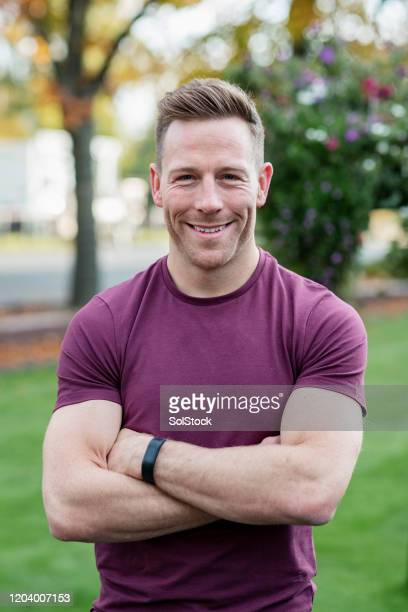 muscular man with arms crossed, smiling at camera - mid adult stock pictures, royalty-free photos & images