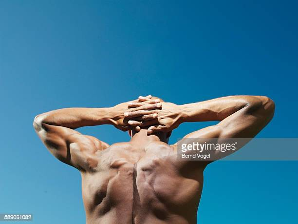 Muscular man with hands behind head