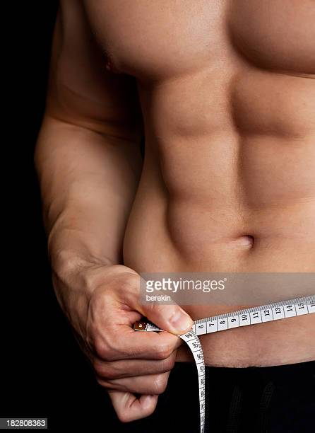Muscular man with tape measure around his waist