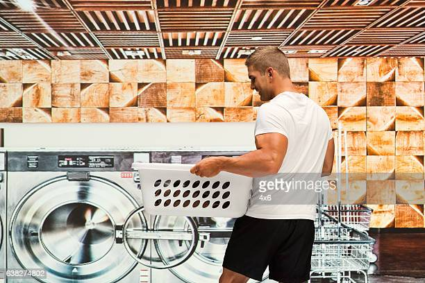 Muscular man working at laundromat