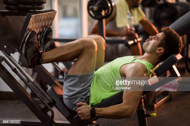 Muscular man working out on a leg press in gym.