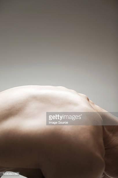 Muscular mature man bending over, abstract