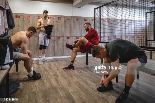 muscular men at a locker room preparing for a training session - locker room stock pictures, royalty-free photos & images