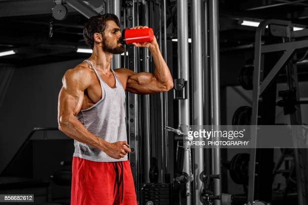 muscular men drink his nutritional supplement - nutritional supplement stock pictures, royalty-free photos & images