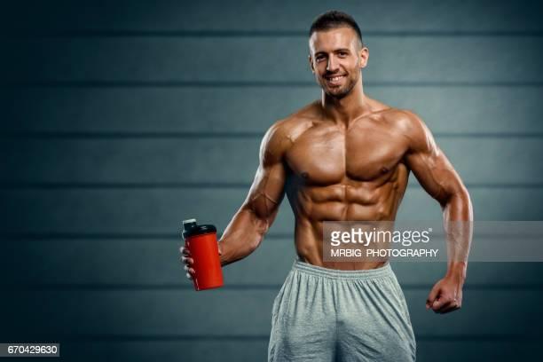 Muscular Men Holding Nutritional Supplement Drink
