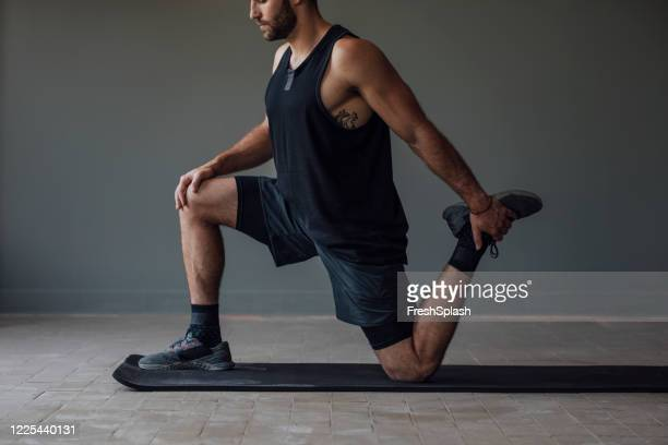 muscular sportsman stretching his legs to warm up for a workout - home workout stock pictures, royalty-free photos & images