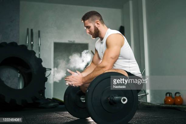 muscular weightlifter clapping hands before workout at the gym with weights - soapstone stock pictures, royalty-free photos & images