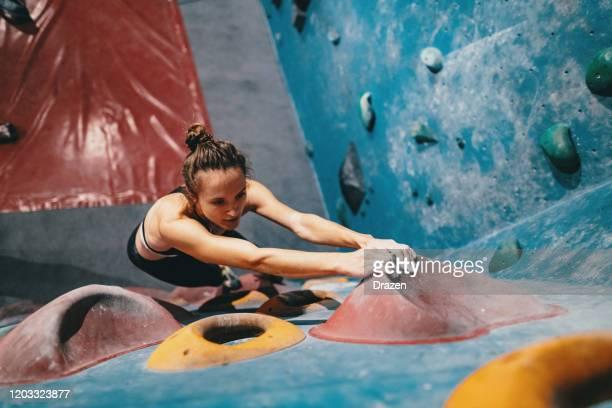 muskuläre frau beim boulder-klettertraining - erwartung stock-fotos und bilder