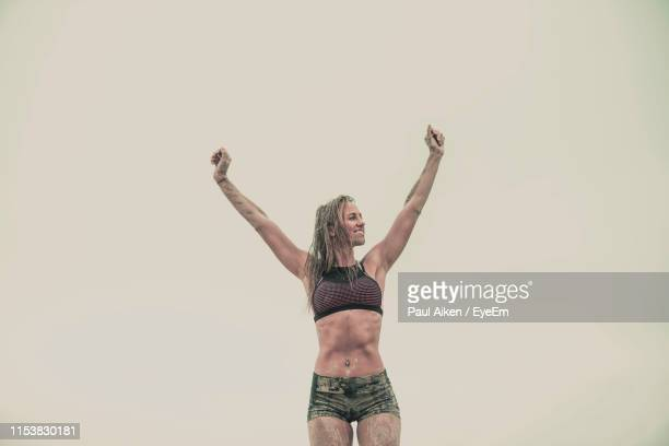 muscular woman standing against clear sky - aikāne stock pictures, royalty-free photos & images
