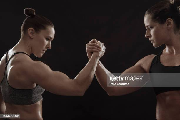 Muscular women gripping hands