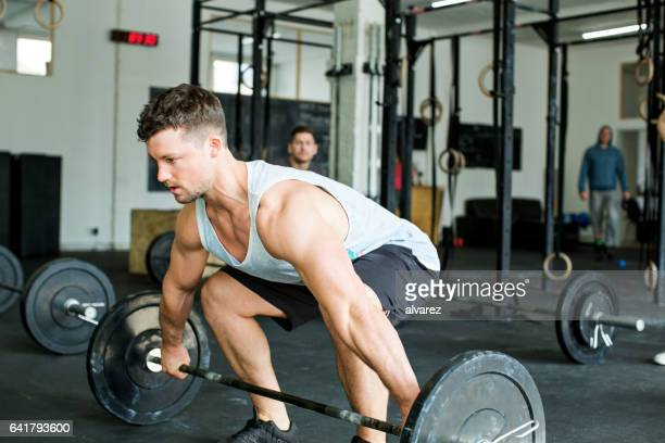 Muscular young man exercising with heavy weights