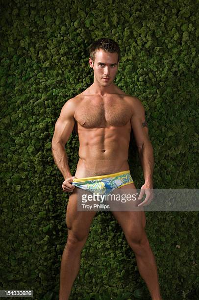 muscular young man standing in front of green moss wall - hairy chest stock photos and pictures