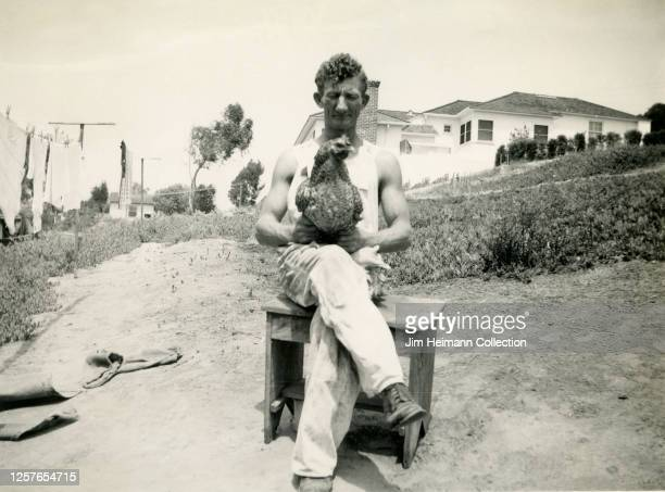 A muscularlooking man in white sleeveless overalls sits on a wooden stool while holding a chicken circa 1942